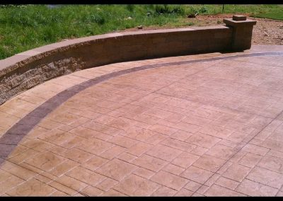 large stamped patio with brick wall