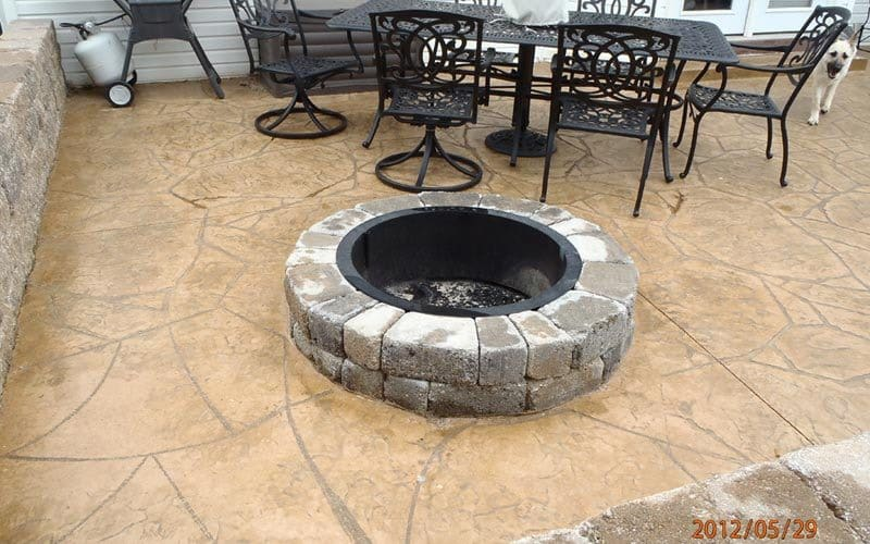 stamped patio with firepit and retaining wall